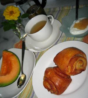 白い丸皿にシナモンロールが2個。その向こうに白いカップに紅茶が、その隣の四角いお皿にメロンの1/4切り。薄い水色のガラスの小鉢にヨーグルトが入っています。透明の丸い小さなグラスに黄色いバラが一輪挿してあります。