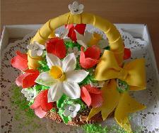 花籠。白とオレンジの可愛い花が小さな持ち手のついた籠いっぱいに生けられています。持ち手には黄色いリボンが巻きつけられ、付け根の部分で大きな蝶結びにされていて、華やかさを添えています。