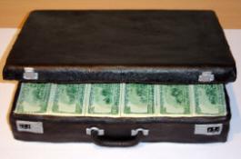 黒いアタッシュケースにきっちり詰め込まれたドル札。口が開けられ中のお札が見えています。これだけあったら・・・・・