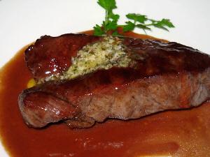 ステーキのアップ画像。こんがり焼かれたお肉、ソースは濃い目のワイン色、お肉の上にはハーブバター、脇に添えたイタリアンパセリの緑が引き立っています。