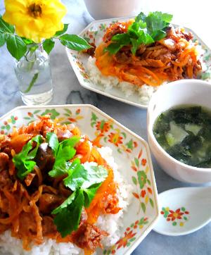 八角形の中華皿に白いご飯、その上に豚キムチ、トッピングに三つ葉、こちらも白、赤、緑の彩り。小さな丸い器にスープが入っています。わかめと餃子入りのスープ。