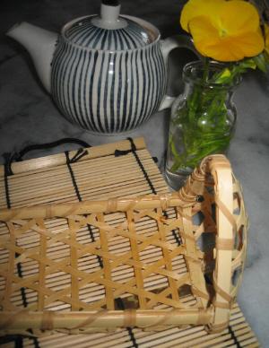 広げたすだれ状の上に乗っている中身の無くなった竹細工のおにぎりの籠。三角形の形に作られてあります。急須と小さな透明の瓶に黄色い花が挿してあるのが見えます。