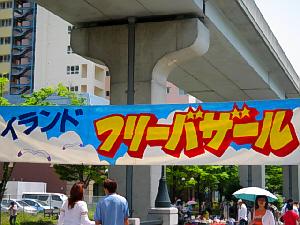 大きな垂れ幕に、アイランドフリーバザールと書かれてあります。背景は白い雲と青空、カモメも描かれてあります。