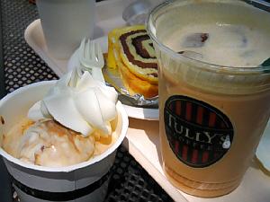 タリーズコーヒーのロゴの入ったカップには、キャラメルラテが入っています。隣の小さめのカップに入っているのは、アイスクリーム。カップの向こう側に渦巻状のケーキが見えています。