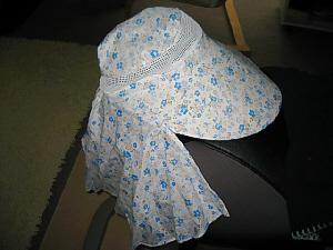 白地にブルーの小花模様の布製の帽子、襟足部分に長い垂れ幕のような布がついている帽子です。