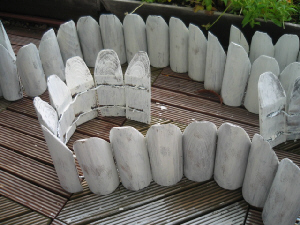 小さな木の柵。丸い木を縦割りにして先を斜めにカットしたものを針金で繋いであるもの。まだらに白く塗られています。