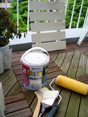 変色してきたウッドデッキの上に無造作に置かれているペンキ缶と、室外機の上部蓋の部分を白く塗って乾かしているところ。ローラーや刷毛が転がっています。
