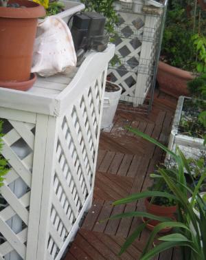 エアコンの室外機のカバーが2台分、白く塗られて並んでいるところ。周りの木製のプランターや鉢も白く塗られています。