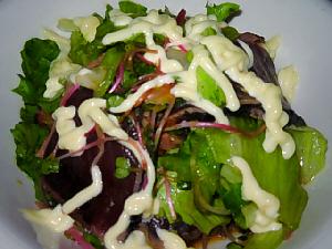 サラダ。緑の野菜とカツオの濃い赤が混じりあい、上にかけられたマヨネーズの白い色が、全体を引き締めています。