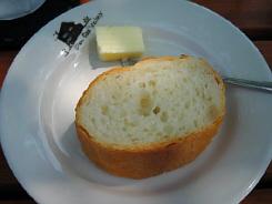 丸い白皿に取り分けたパン。お皿は淵に黒でレストランのシルエットが描かれたオリジナルなお皿です。