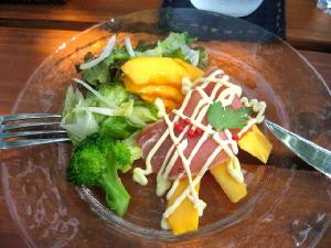 透明なガラスの平皿に盛られたサラダ。野菜の隣にスライスしたパパイヤの上に生ハムが乗せてあります。ドレッシングとマヨネーズがかかっています。
