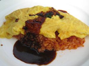 オムライスのアップ画像。赤いご飯の上に黄色い玉子、とろりとかかったソースは黒味がかったドミグラスソースのようです。真っ白なお皿にソースの色が映えています。