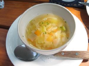 白いソーサーの上に丸いスープカップ。野菜の煮たものが入っています。
