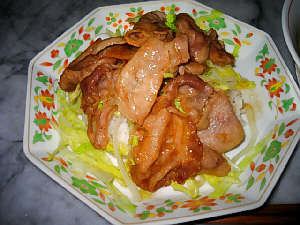 中華皿に少量のご飯、たっぷりのレタスの千切り、その上に薄切り豚肉のしょうが焼きが乗った、サイドディッシュ。