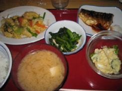 赤い塗りのトレーの上に、ご飯、味噌汁、青なのお浸し、焼き鯖、ミニポテトサラダ、豆腐の変わりに麩を使ったチャンプルーが並んでいます。