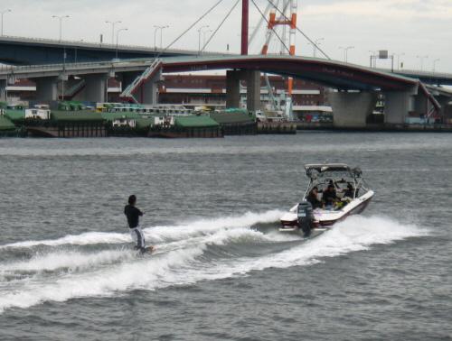 上記とは逆の方向に走っているボートと滑っている人。ボートの中の人たちがこちらを見ています。今度は転ばずにしっかり波をかわしています。
