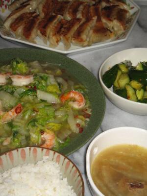 ご飯とスープ、その向こうに白菜の煮たものが入った緑のお皿、その隣にきゅうりの漬物が入った白い器、更にその奥に八角形の大きな中華皿に餃子が並べられています。