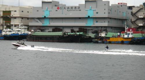 疾走するボートの後ろに水上スキーのように紐が伸びて、スキーではなく板に乗った男性が水の上を滑っているところ。背景はまさに運河の光景そのもので、倉庫や小さな船が沢山並んでいます。