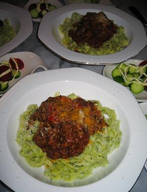 八角形の白いお皿に入ったパスタ。ミートソースのようなものが上にかかっています。涙型のお皿にきゅうりとプチトマトが入れられ、マヨネーズがかかっています。