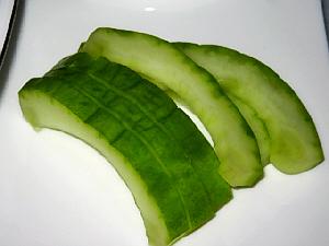 四角い平たい白いお皿に、瓜のお漬物がスライスして乗っています。あっさり塩味なのでサラダ感覚で。鮮やかな緑色が綺麗です。