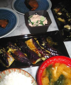 ご飯、味噌汁、その向こうに長方形の黒いお皿に焼きなすが並べられ、更にその奥に、四角い黒の小鉢にきゅうりとツナのサラダ、その隣側にブリが入ったブルーのお皿が並べられています。