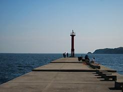 都志港のトレードマーク、防波堤の先端に立つ赤い灯台。小さなものですがここを航行する漁船には、安心の道しるべとなっているのでしょう。灯台の向こうには青い海が広がっています。