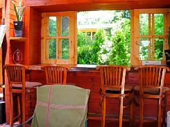 窓辺のコーナー。どっしりとした木製のカウンターに、木製の椅子。窓も木造りで外の緑が実に良くマッチしています。