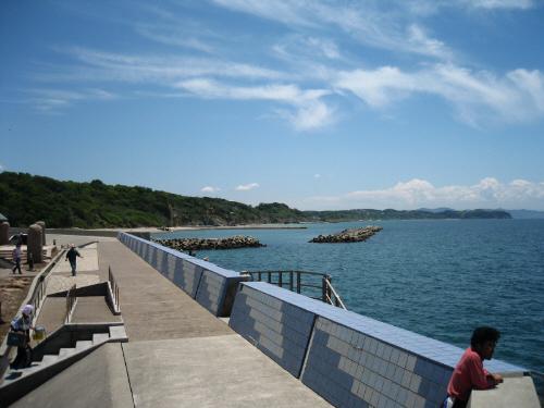上の写真とは反対の方向を写した一枚。長く続く防波堤の先には白い小さなビーチと緑の山が。真っ青な空には少々の雲がアクセントに。穏やかで美しい淡路島の光景です。