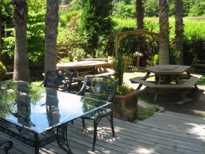 木陰に配置されたガラスのテーブルと真鍮の椅子。向こう側には木製のテーブルとベンチも設えられてあります。