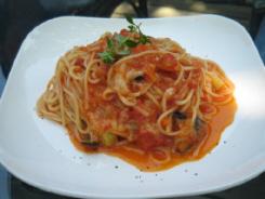 トマトソースのパスタ。白いお皿にトマトの色が映えています。