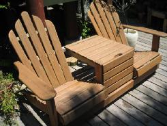間にテーブルを挟んだ、2つ連なった木のベンチ椅子。背もたれが高くて首まで支えていい感じです。