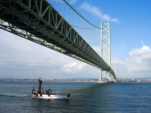 明石海峡大橋をやや下側から眺めた一枚。明石方面へ続く箸の下を1艘の船がくぐっている瞬間です。遠くに明石の町並みを望むことが出来るほど良いお天気でした。