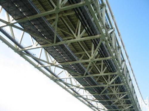 橋の裏側の部分を見上げて撮ったアップ画像。幾何学模様のように組まれた鋼材で端が補強されていて、芸術作品のようにも見えます。橋の上には青空が広がって、空にかかる橋のように見えます。