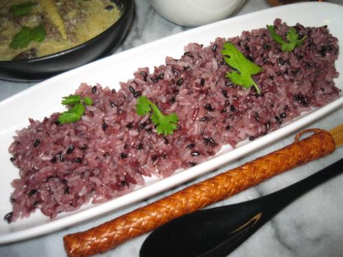 古代米のアップ画像。小豆色に染まったご飯が綺麗です。もう少し古代米の分量を減らすと、淡いピンク色のご飯になります。上に散らした香草の緑が、ご飯の色を一層鮮やかに見せています。真っ白な器にご飯の色も映えています。