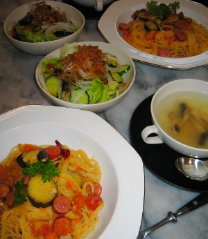 八角形の白いお皿に盛られたパスタ。その隣に黒いソーサーに白いカップのスープ、小さなスープスプーンが添えられてあります。その向こう側に丸い白いボウルに入ったサラダが並んでいます。
