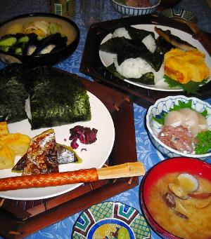 六角形の竹で作られた器の上に白い丸いお皿が乗せられ、その上におにぎり二個、焼き魚、玉子焼き、柴漬けが盛られています。竹の箸は竹で編んだ筒状の箸袋に収められて、お皿の上に渡してあります。アサリの味噌汁椀、刺身の盛られた小さめの丸い器、そして、茄子、きゅうり、白菜の漬物が盛り込まれた大きめの器が奥に見えています。