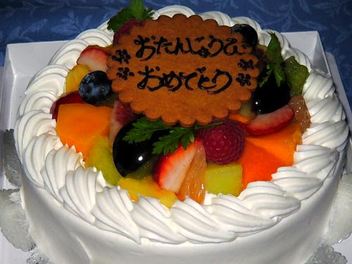 真っ白な生クリームで包まれたホールのケーキ。色とりどりのフルーツがたっぷり乗っていて、その周りはクリームのデコレーションで囲まれています。真ん中におたんじょうびおめでとうと書かれたクッキープレートがどんと乗っかっています。