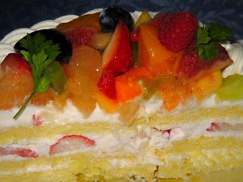 上記のケーキを半分にカットし、切り口を見せている画像。3層になったスポンジで、生クリームとイチゴが挟まれています。