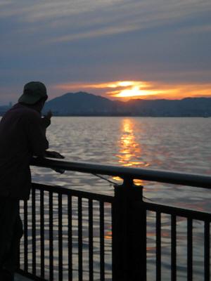 釣りざをを垂らしている男性のシルエットの向こうに、山間に沈みかけている夕日が海に反射して、オレンジのラインを作っています。穏やかな神戸港の夕暮れの一こま。