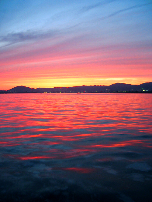 うっすらと青い空が残っている状態で、日が山間に沈みかけ、金色の帯を山の上に広げています。海面はオレンジ色に輝いて遠く海岸線に点り始めた明かりが幻想的です。