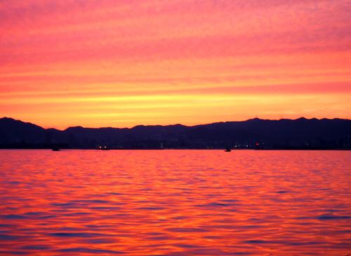 金色の帯の部分のアップ画像。海も空もオレンジ色に染まり、神戸の町並みと山並みが黒いシルエットになって浮かび上がっています。海面を行き交う船も黒いシルエットにして浮かび上がらせています。正にオレンジ色の芸術!