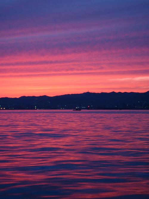 完全に日が落ちる少し手前の状態は、オレンジ色から紫色へと色合いが変化していきます。この世には紫の濃淡しかないのではないかと思える風景。町の明かりが一層輝きを増してきています。涙が出そうになるくらい美しい光景でした。