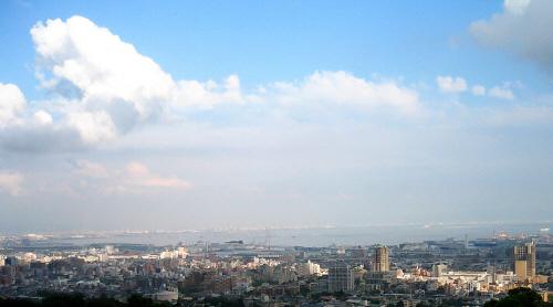 神戸の町並み、その向こう側に大阪湾、厚い雲の合間に爽やかな青空が顔を出し、街に筋のような光があたっています。光が当たった部分だけが白く浮かび上がって、町並みにアクセントをつけています。