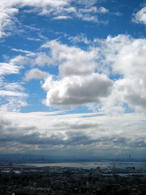 町並みの向こうに大阪湾が広がり、町全体は濃いグレーに包まれています。海もまた同じように鈍い色合いを放っています。空だけが真っ青な青空が顔を覗かせ、町並みや海の色合いとは対照的に、爽やかさと華やかさを身にまとっています。空全体は厚い雲に覆われていて、一部雲が割れて出来上がった不思議な幻想的な世界です。