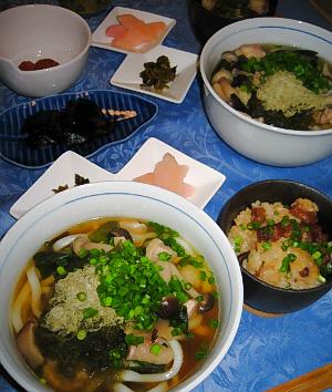 白い丼にうどん、その隣の小さな黒い器にご飯物、その向こう側に漬物が入ったひし形がふたつくっついたような白いお皿、更にその向こうの青い葉っぱ型のお皿には佃煮が盛られています。