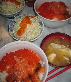 サーモンとイクラどんぶり、隣にあら汁、その向こうに千切りキャベツのサラダが並んでいます。