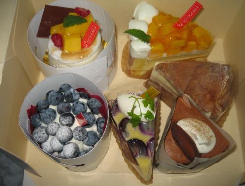 ムース系のマンゴーの角切りの乗ったもの、巨砲のタルト、ブルベリーのタルト、蒸しチョコケーキ、マーブルチョコケーキ、マンゴーのショートケーキの6種類が盛り込まれた箱の中身。
