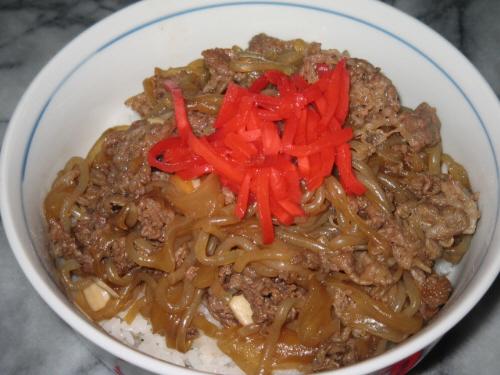 白い丼に盛られた牛丼、真っ赤な紅生姜がアクセントです。