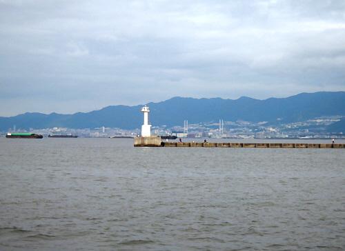 長く突き出た防波堤の突端に白い小さな灯台が立っています。その向こうに見える山並みは六甲山のようですね。