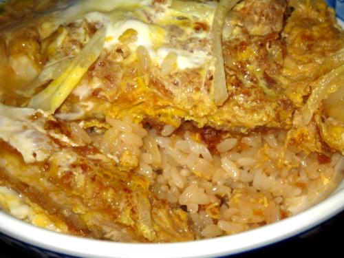 カツ丼のアップ画像。ご飯にしっかりツユが染みこんでいます。玉子とカツ、時々無性に食べたくなる取り合わせです。